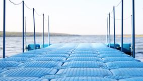 Blue floating plastic pontoon pier with rope railings rocking on waves at lake or river beach. Dock for small boats and. People walkway stock footage