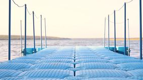 Blue floating plastic pontoon pier with rope railings rocking on waves at lake or river beach. Dock for small boats and. People walkway stock video footage