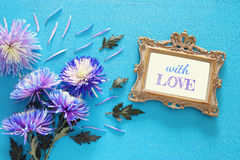 Blue flowers and blank victorian photo frame on wooden background. Top view image of spring beautiful blue flowers and blank victorian photo frame on wooden stock image