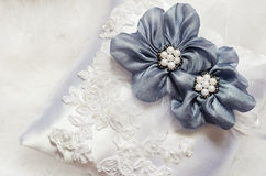Blue flowers on satin pillow. Blue textile flowers on white satin pillow Stock Image