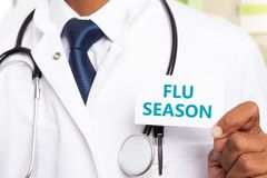 Blue flu season text held by physician. Blue flu season text on white business card held by indian male physician or medic close-up royalty free stock images