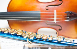 Blue flute detail with violin and score. Blue flute detail with out of focus wooden violin and score Stock Photography