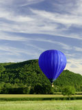 Blue flying hot air balloon Royalty Free Stock Photos
