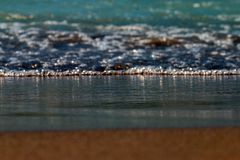 Blue foamy waves coming to brown sandy beach. stock images