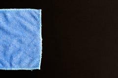 Microfiber. Blue folded microfiber cloth on black table stock photography