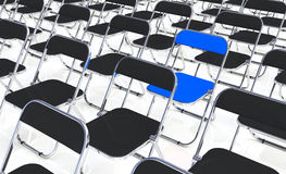 Blue chair. A blue folding chair among many black folding chairs Royalty Free Stock Photos