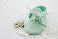 Blue fondant sugar shape baby bootees and silver charms on white lace background. Photo of blue fondant sugar shape baby bootees and silver charms on white lace royalty free stock image
