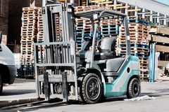 Blue fork lift truck. Big blue fork lift truck outdoor near wooden blue, red and natural pallets stock photo