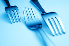 Blue forks. Three blue forks arranged in cold blue light Royalty Free Stock Image