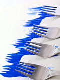 Blue Forks. Four forks dragged through blue acrylic paint on the diagonal royalty free stock photo