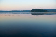 Calm lake at sunset. Blue forrest lake at sunset Royalty Free Stock Photo