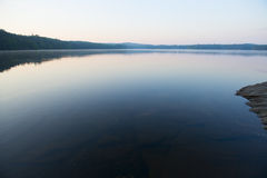 Calm lake at sunset. Blue forrest lake at sunset Royalty Free Stock Photos