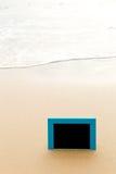 Blue framed blackboard sitting in sand at beach Stock Image