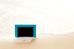 Blue framed blackboard sitting in sand at beach Royalty Free Stock Images