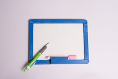 Blue framed whiteboard with a green pen. On white background Stock Photo