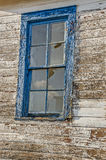 Blue-framed Window. Broken panes and reflections in an old window framed with blue peeling paint and loads of texture Stock Photos