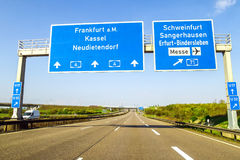 Blue freeway sign over the road in Germany on sunny day Stock Photos