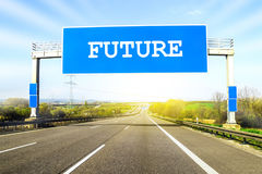 Blue freeway sign over the road on sunny day with word Future on stock photos