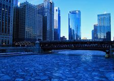 Blue and frigid winter morning in Chicago while el train passes over Chicago River. Blue and frigid winter morning in Chicago while elevated `el` train passes royalty free stock image