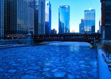Blue and frigid winter morning in Chicago while el train passes over Chicago River and buildings reflect cityscape. Blue and frigid winter morning in Chicago royalty free stock images