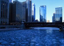 Blue and frigid winter morning in Chicago while el train passes over Chicago River and buildings reflect cityscape. Blue and frigid winter morning in Chicago royalty free stock photography