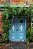 Blue  front door in a historic house with climbing plants at the Royalty Free Stock Photos