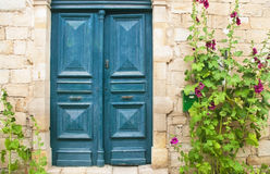 Blue front door with purple flowers Royalty Free Stock Image