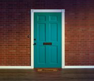 Blue front door with welcome mat. stock image