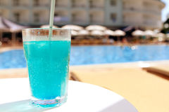 Blue fruit cocktail near pool on the table Royalty Free Stock Image
