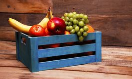 Fruit basket. A blue fruit crate filled with various fruits Stock Image
