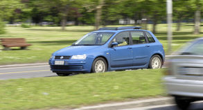 Blue fun. Moving small blue car, blured background Stock Image