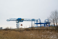 Blue gantry crane with winch over dull sky. Royalty Free Stock Photo