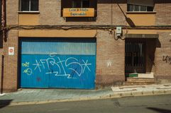 Blue garage gate and door on a brick building at Caceres royalty free stock photography