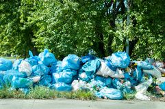 Blue garbage bags full of trash left on the street pollute the city. Blue garbage bags full of trash left on the street pollute the city Royalty Free Stock Photography