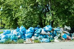 Blue garbage bags full of trash left on the street pollute the city. Garbage in the city Royalty Free Stock Images