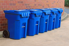 Blue garbage bins. Line of 5 blue garbage bins against a brick background Royalty Free Stock Images
