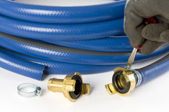 A blue garden hose. A brass coupling is mounted to a garden hose royalty free stock image