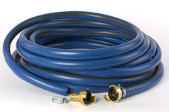 A blue garden hose. With brass coupling pictured on a white background royalty free stock photography
