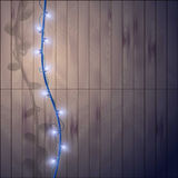 Blue garland with light bulbs on a wooden background. Stock Photography