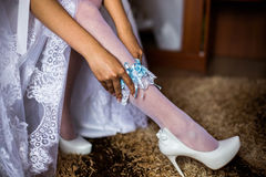 Blue garter on leg. Of the bride morning bride, the bride wears a garter on the leg, the preparations for the wedding Royalty Free Stock Image