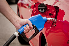 Pumping fuel into a vehicle. Hand holding a blue gas nozzle pumping fuel into a red vehicle Royalty Free Stock Image