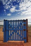 Blue gate on beach. With dramatic sky Stock Images
