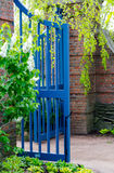 Blue gate into the garden Royalty Free Stock Photos
