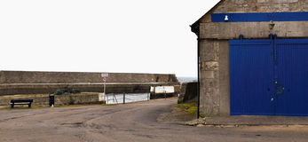 Blue gate and speed limit. Blue gate next to a road with speed limit heading to the sea at Lossiemouth in Scotland Stock Image