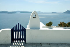 Blue gate wicket and white fence. Mediterranean sea and Santorini caldera on the background. concept of leasure, freedom, luxury Stock Photo