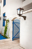 Blue gates in white wall with gas lamp at greek style Stock Photography