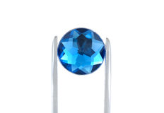 Blue Gem. Photo of Tweezers Holding a Blue Gem Stock Image