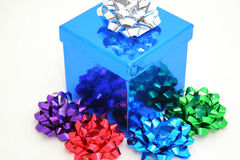 Blue gift and bows. A sparkling blue gift box with multi-colored bows. White background Royalty Free Stock Images