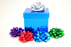 Blue gift and bows. A sparkling blue colored gift box with multi-colored bows. White background Stock Photo