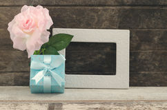 Blue gift box with blank frame and oink rose. Vintage filtered style Stock Image